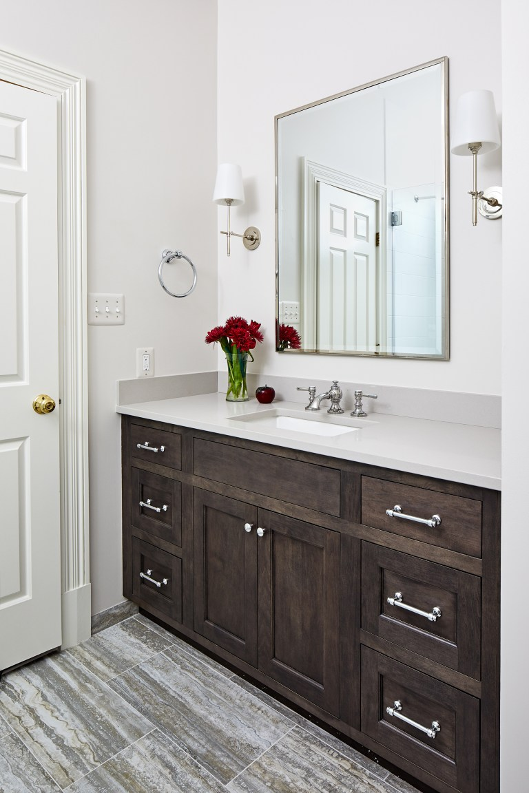 wood vanity with side wall lighting and rectangular mirror