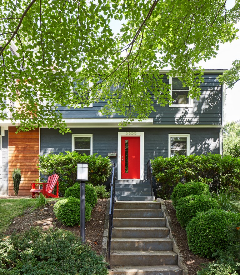 blue house with red door and wood panel detail modern design