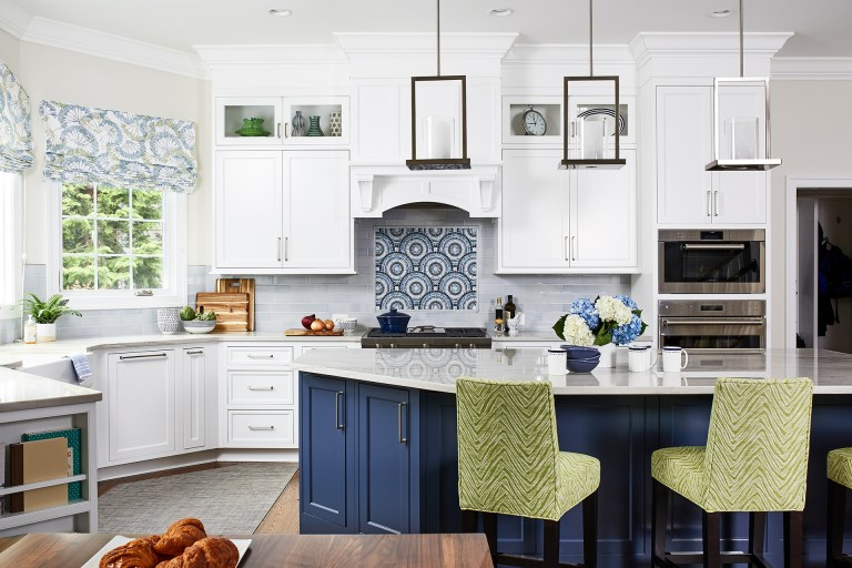 white kitchen cabinets with white and blue kitchen island, hard wood floors