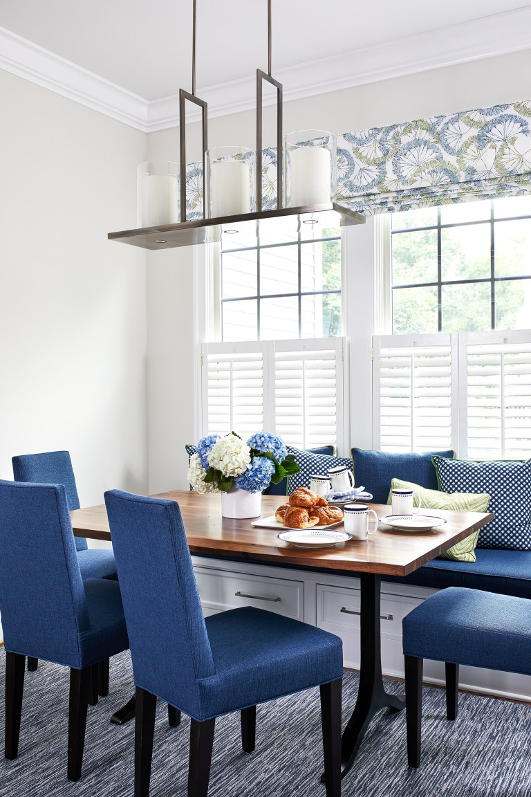 blue kitchen breakfast nook features a built-in bench window seat topped with blue cushion and blue pillows under a bay window facing a wood dining table with blue cushion dining chairs