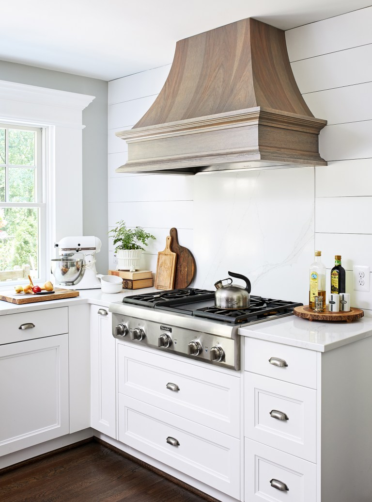 wooden hood range above stainless stain 5 sealed burners cooktop with white cabinets with pull handles