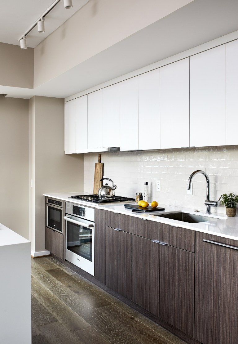 Kitchen remodeling with white brick backsplash, chrome gooseneck faucet and brown cabinets with pull handlers