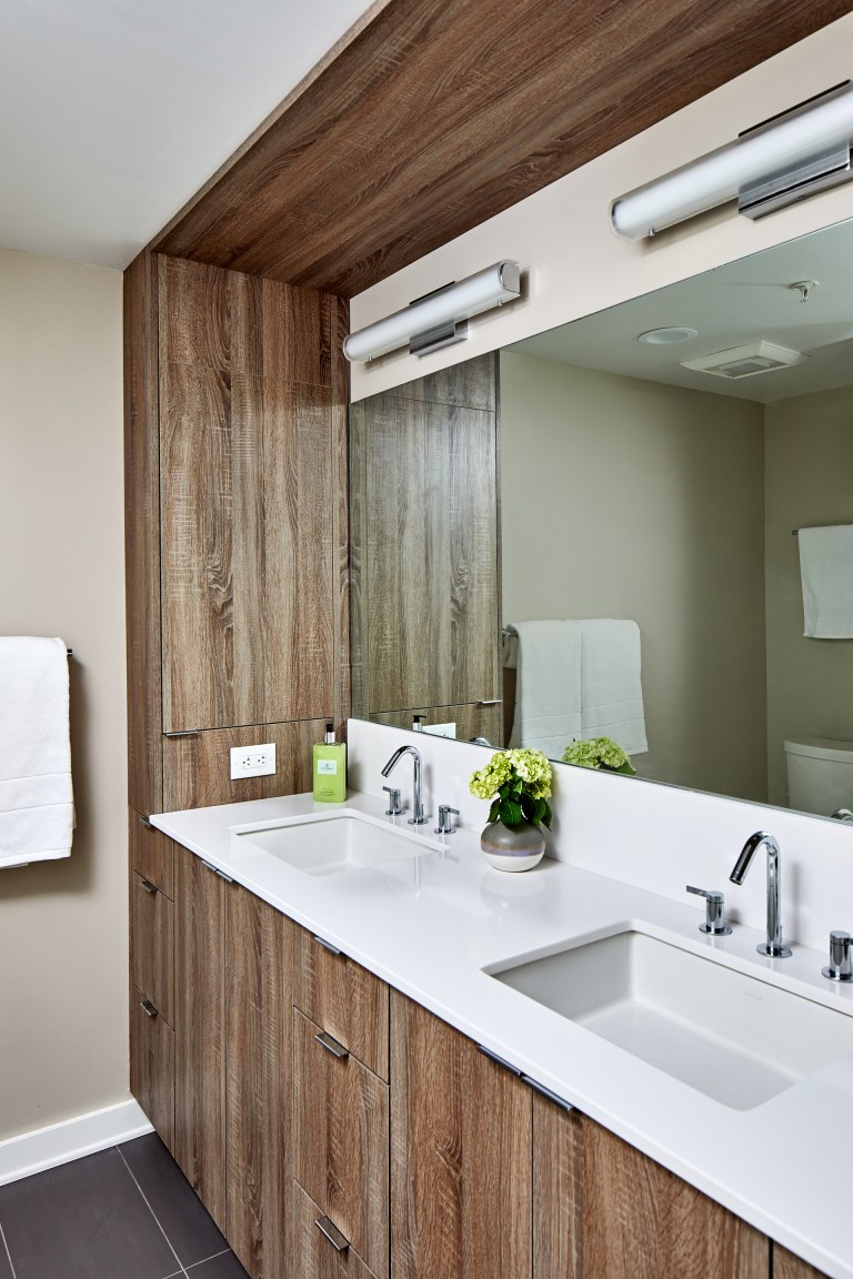 Remodeling company bathroom with wide mirror that runs length of vanity with wood cabinets with pull handles and white rectangular sinks