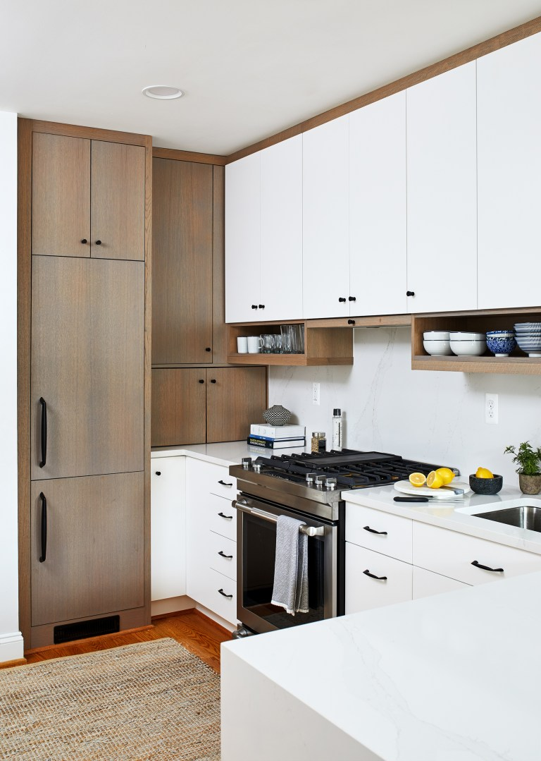 Dc home remodeler kitchen with brown tall wooded cabinets storage with black pull handles and knobs