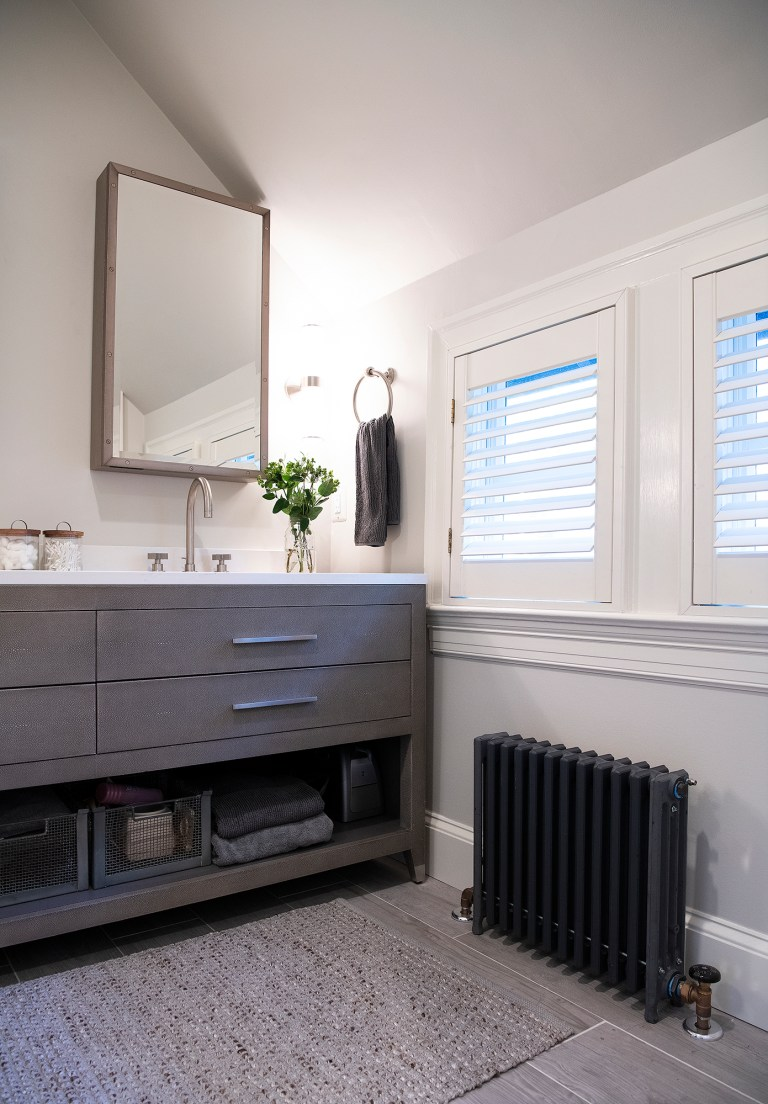Two small windows above a cast iron hot-water radiator