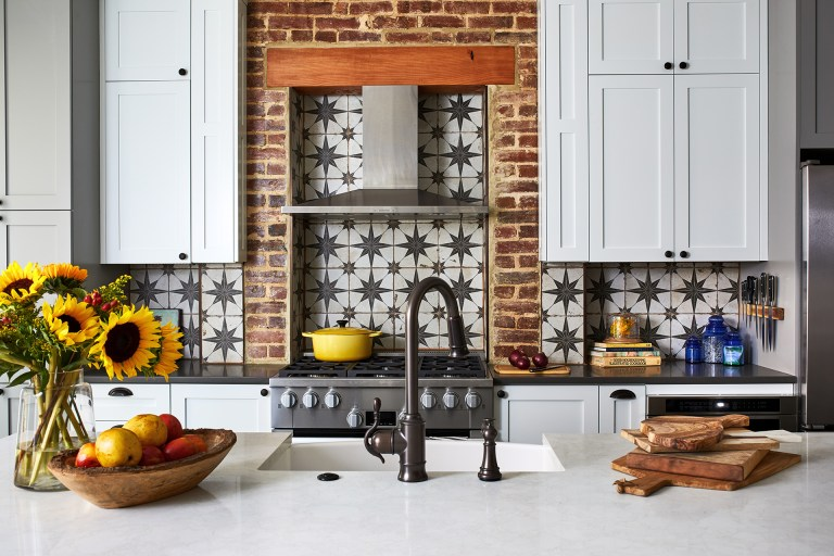 Thin brick arch surround around the cooktop with a tile backsplash and stainless-steel hood range