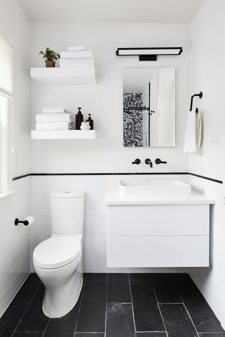 black faucets with light fixture add small but strong accents to this mostly white bath