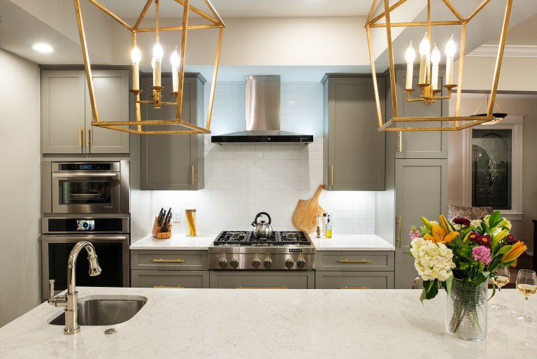 Large kitchen island with above gold light fixtures