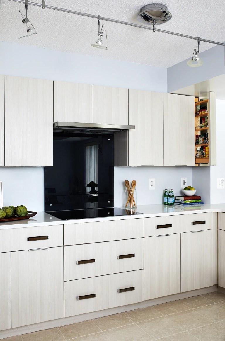 White cabinets doors, black back splash, black stovetop with kitchen track lighting