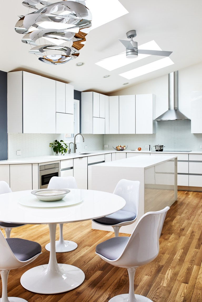 ceiling over a white kitchen island with round white table