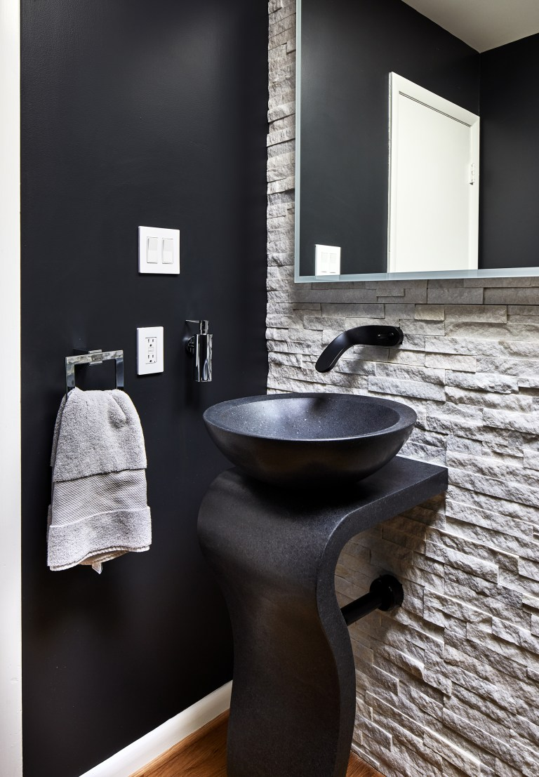 exposed brick bathroom with black single washstand