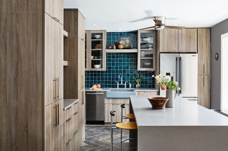 kitchen with natural wood cabinetry teal tile and island with waterfall edge countertop and seating
