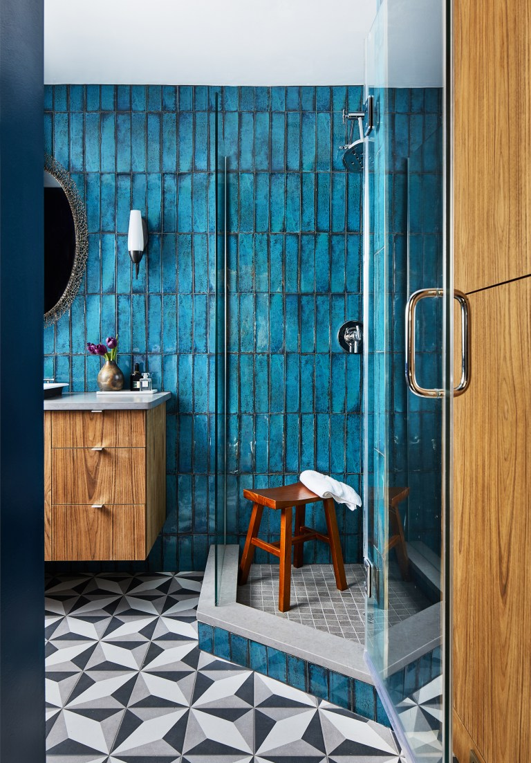 renovated bathroom with geometric tile floor shower stall with glass door teal wall tiling and natural wood floating vanity