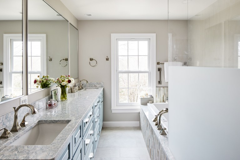 bathroom with marble counter tops with two sinks perfectly placed in between the shower room and the bathtub