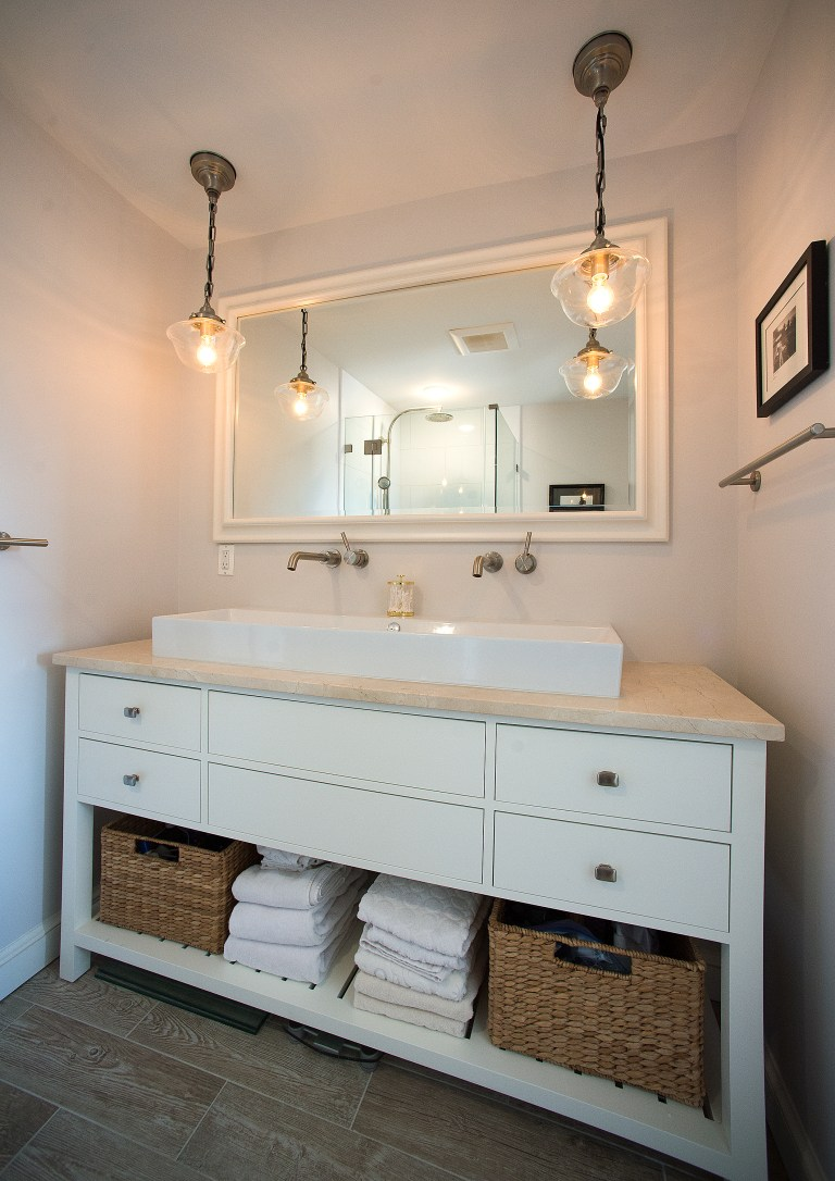 bathroom vanity white cabinetry drawer and shelving built in storage double sink wall mount faucets pendant lighting