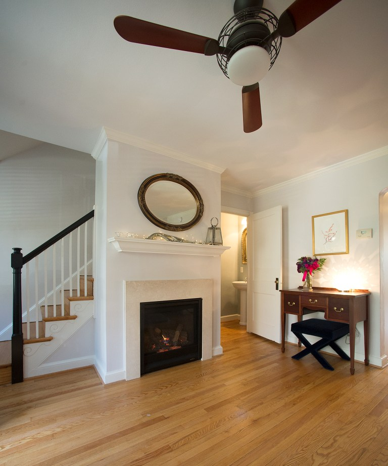 traditional style entry area with wood floors fireplace and staircase neutral color palette