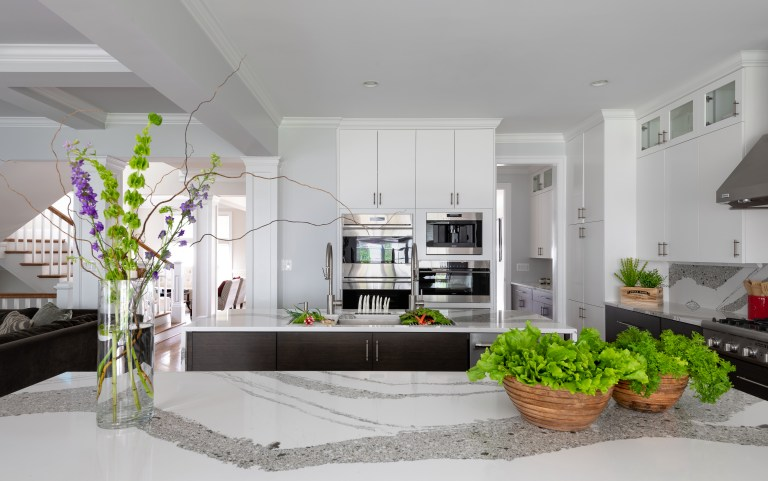 white cabinets with pull handles and kitchen island with sink
