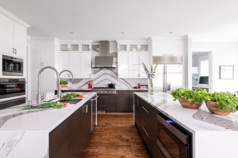 open plan kitchen with double kitchen island, double sink, with white custom cabinetry matching backsplash and stainless-steel kitchen sink faucet with pull out sprayer, fingerprint resistant