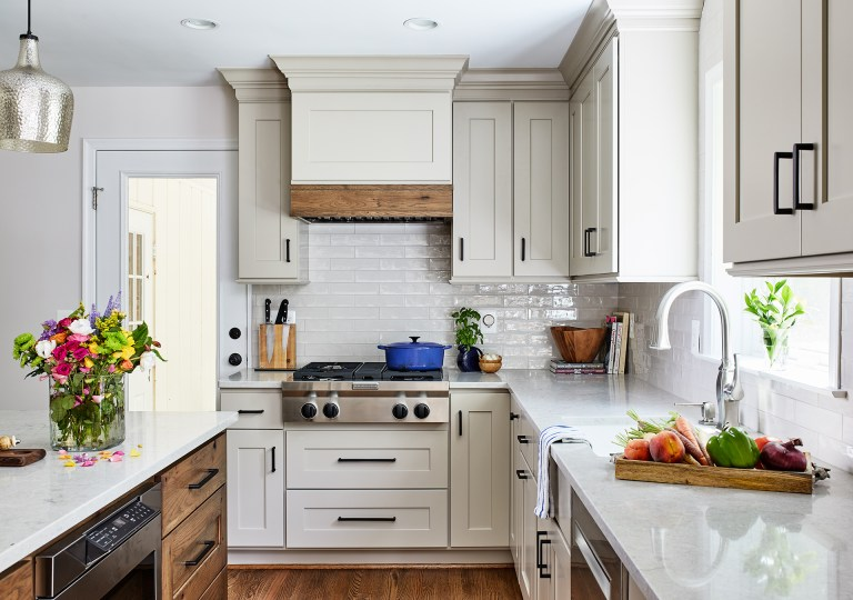 transitional kitchen with subway grey tiles backsplash freestanding cabinets, vent hood over the gas cooktop with 4 burners in stainless steel