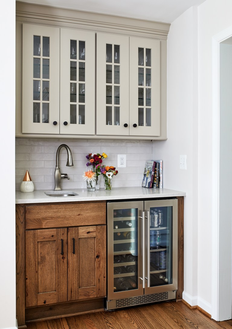 white glass cabinets above small island with marble top and single sink with wine cooler fridge