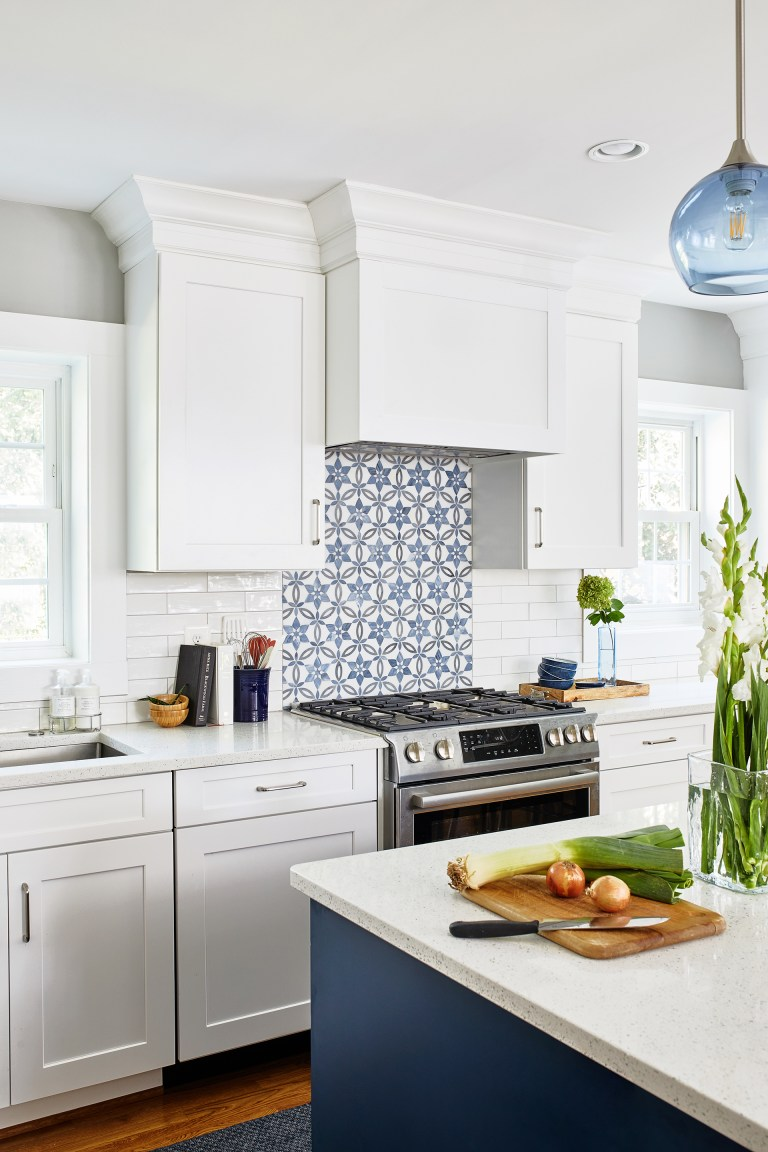 case kitchen design with blue and white backsplash, white cabinets with pull handles
