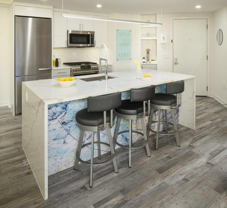 case design kitchen in DC has LED Linear Pendant packs a lot of lumens into an ultra-thin linear-suspension frame, minimal lines, maximum light and a marble kitchen island with three seatings