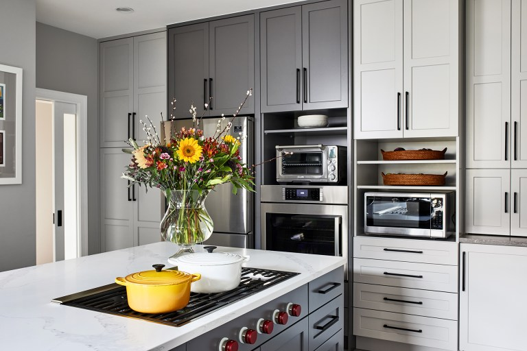 Maryland transitional marble kitchen island with 5 burner, stainless steel appliance, open shelve with built in refrigerator, floor to ceiling grey cabinets, white cabinets with black pull handles the refrigerator in the new kitchen is surrounded by great pantry cabinets on one side large island with seating