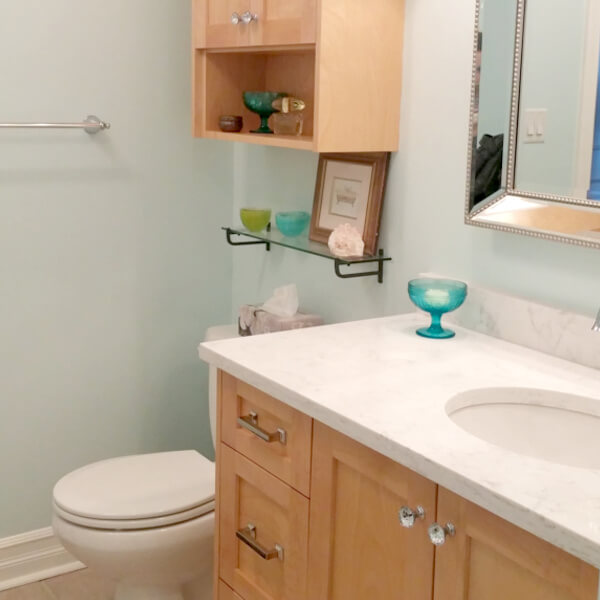 clean white marble vanity with blue glass accent tiles