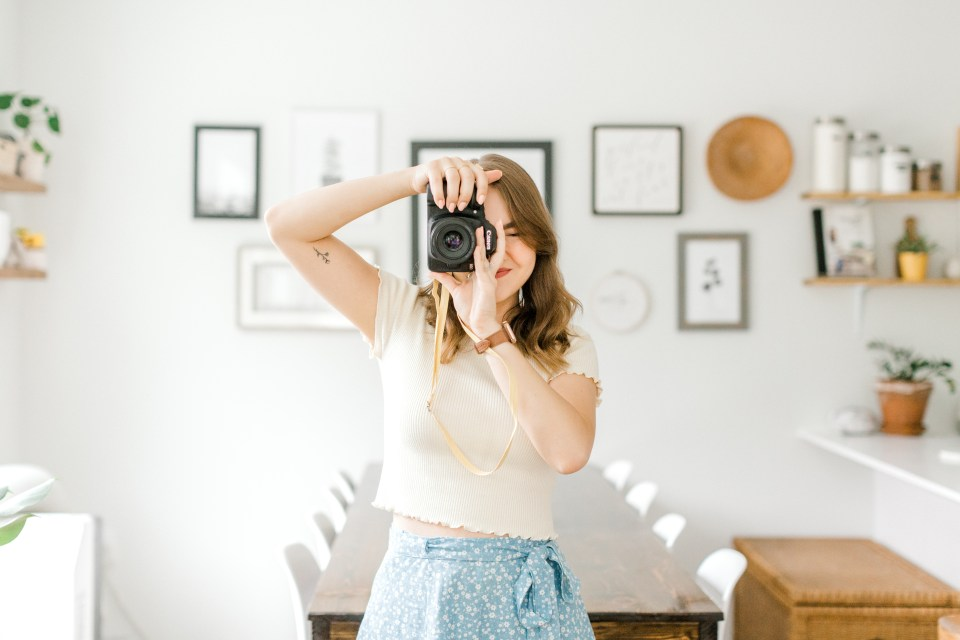 Woman standing in dining room looking through camera viewfinder.