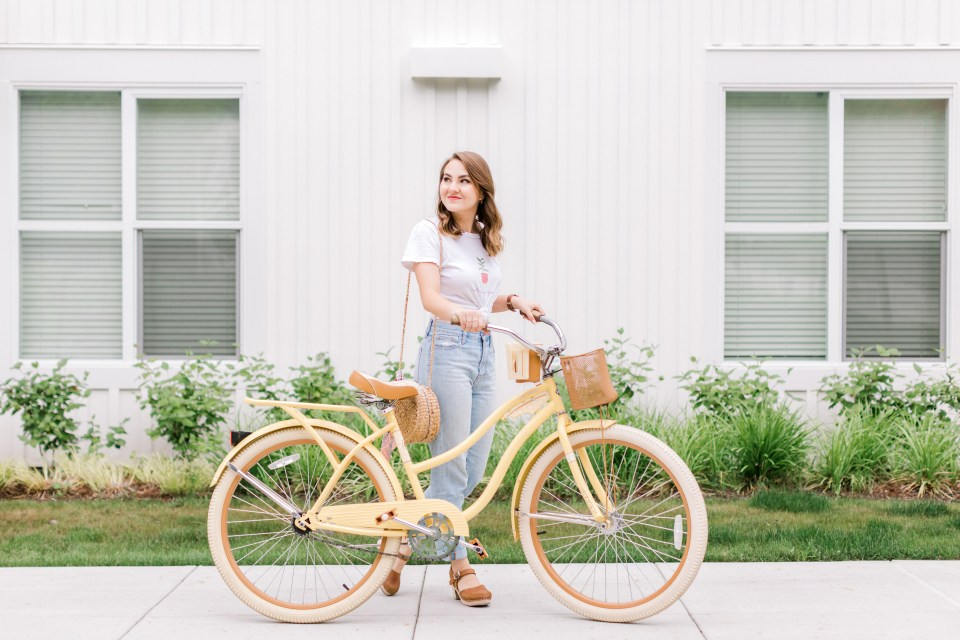 Woman walking with yellow Huffy bicycle in front of white apartment building.