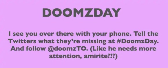 "A slide from the slideshow for Doomzday that reads: ""I see you over there with your phone. Tell the Twitters what they're missing at #DoomzDay. And follow @doomzTO. (Like he needs more attention, amirite???)"""