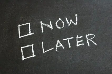 The words now and later written on a chalkboard with checkboxes.