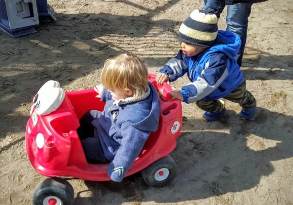 Drive Your Way to Delight at isure.ca! — Little Man Giving His Friend a Push in a Toy Car