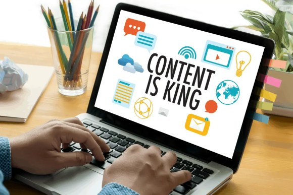 "A shot of a laptop whose screen reads ""Content is King"", describing what is most important for SEO."