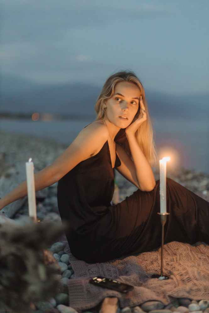 woman in black spaghetti strap dress holding lighted candle