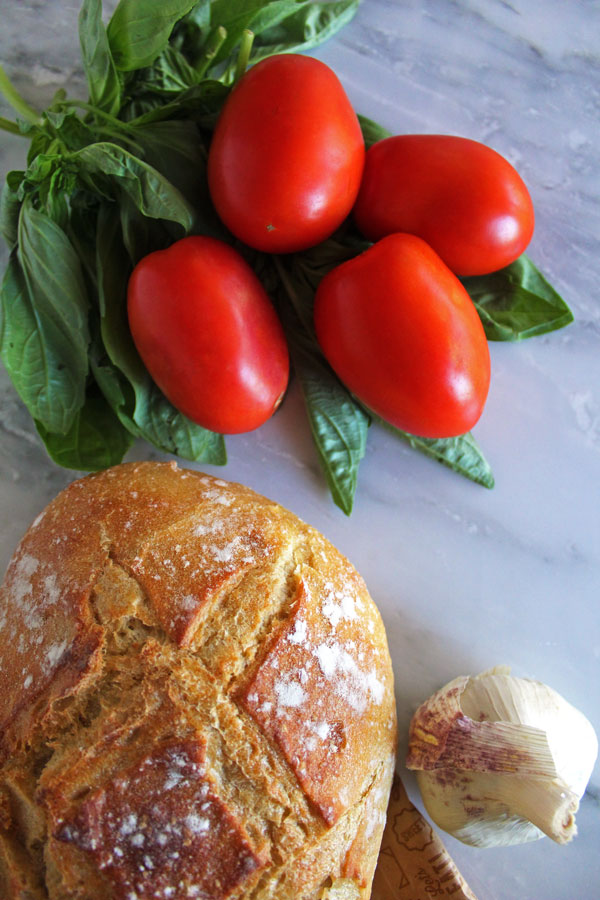 Roma tomatoes, fresh basil, a head of garlic, and a loaf of sourdough bread on a white marble countertop.