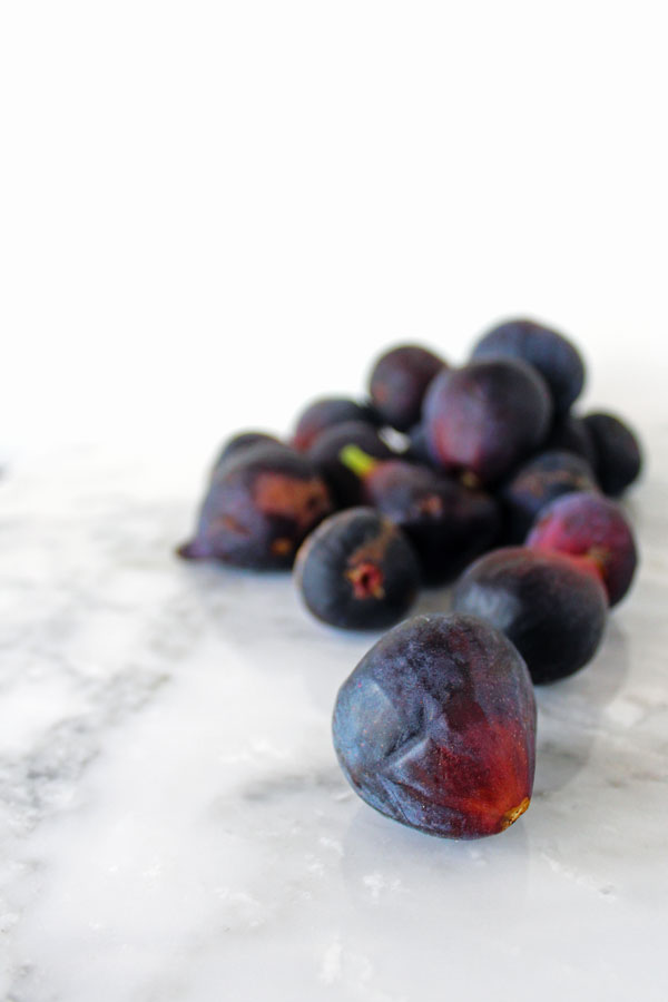 Close up photo of fresh figs on a white marble countertop with a white background
