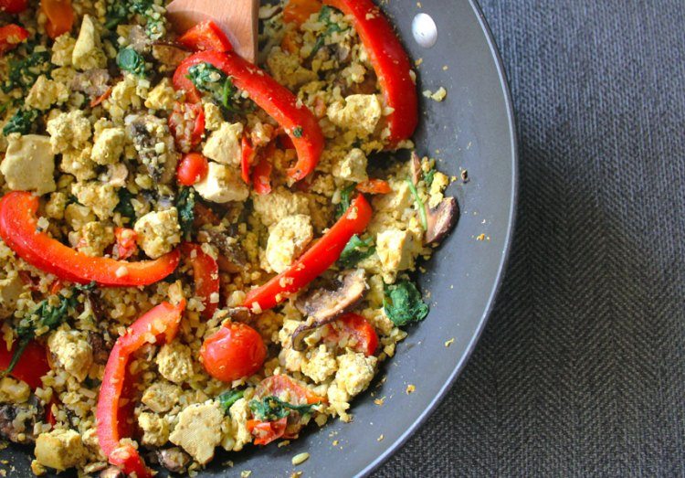 Tofu scrambled with red, orange, and yellow tomatoes, red bell peppers, spinach and cauliflower rice in a large skillet.