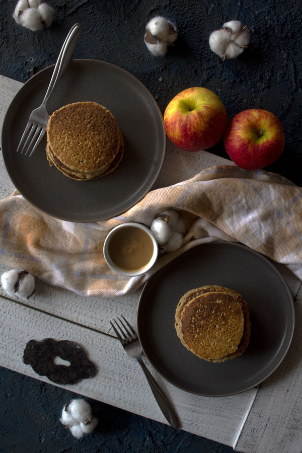 Plated apple pancakes surrounded by caramel sauce, apples and cotton.