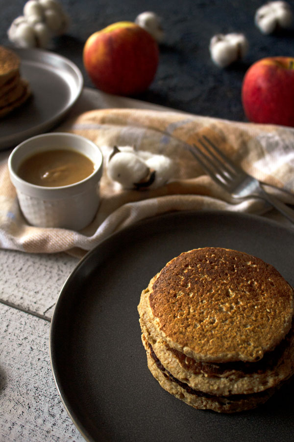 Apple pancakes on a plate with date caramel, apples and cotton in the background.