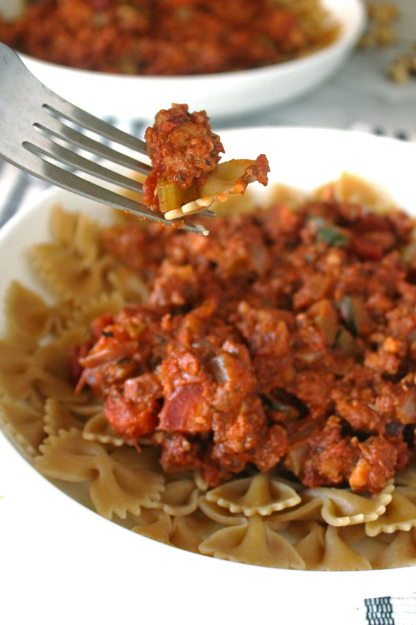 "Pasta and walnut and tofu ""meat"" bolognese sauce on a fork."