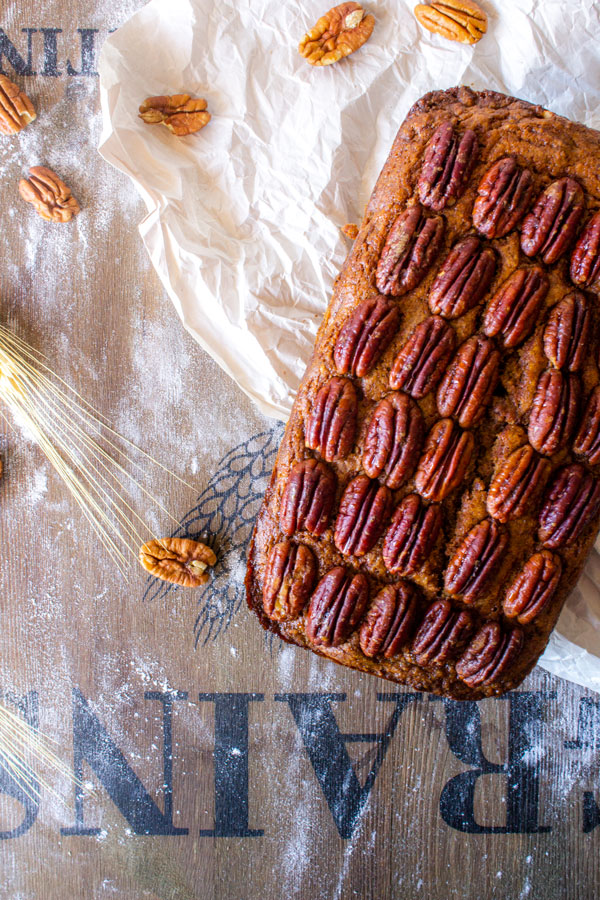 Pecan pie quick bread on a wooden cutting board with wheat and pecan halves.