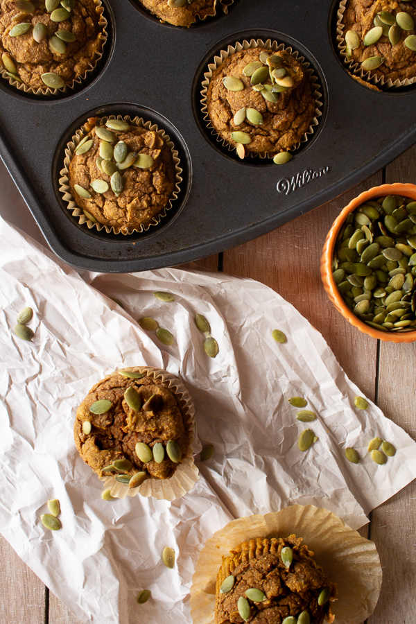 Blender pumpkin muffins in a muffin tin on paper surrounded by pumpkin seeds.