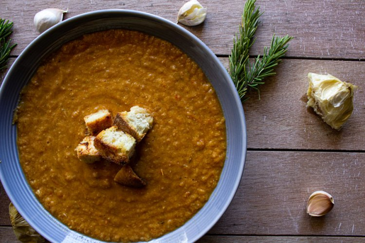 Roasted garlic and tomato soup topped with homemade croutons in a light blue bowl surrounded by rosemary and garlic cloves.