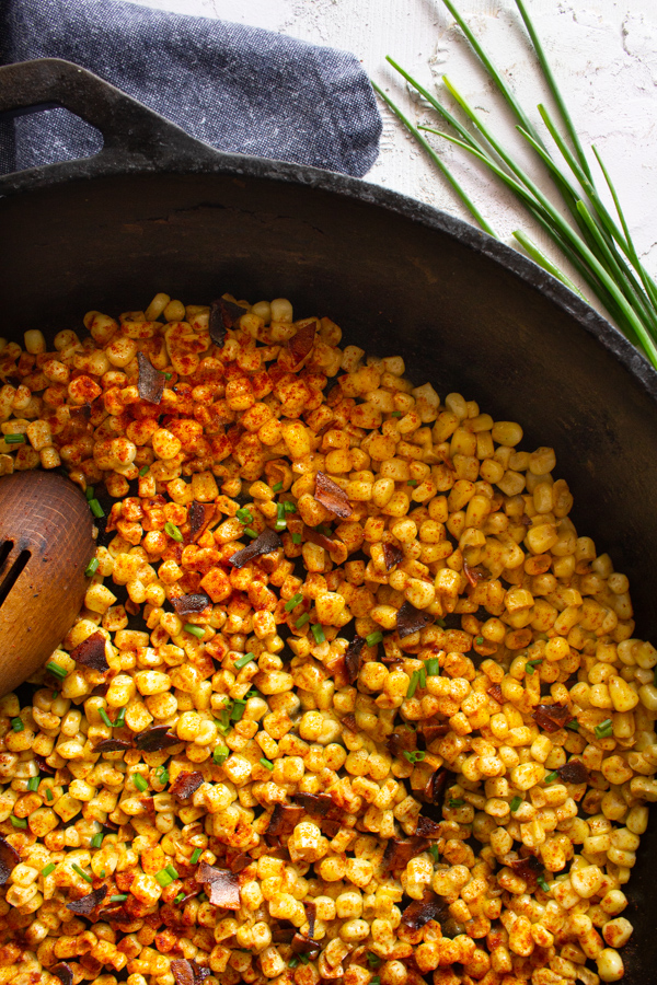 Vegan bacon buttered corn in a large cast iron skillet with a large wooden spoon for serving.