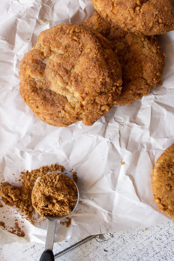 Vegan pumpkin cheesecake cookies on parchment paper with a tsp of pumpkin pie spice.