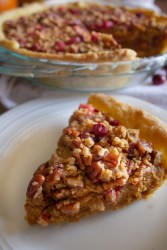 A slice of vegan pumpkin pie with cranberry pecan streusel topping sitting on a white plate with the whole pie resting on a white cloth in the background.