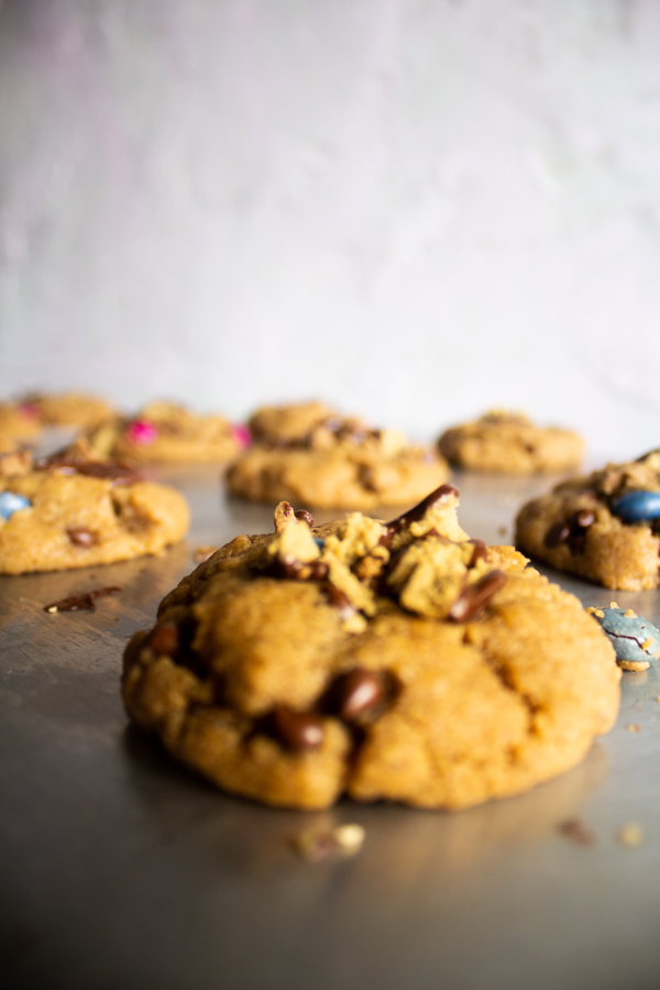 Close up of a batch of chocolate peanut butter cup cookies on a cookie sheet.