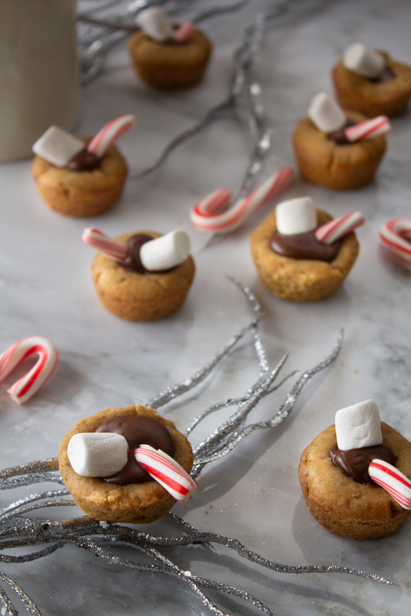 Hot chocolate cookie cups filled with chocolate ganache, a mini marshmallow, and a candy cane on white granite counter surrounded by silver glitter stands and candy canes.