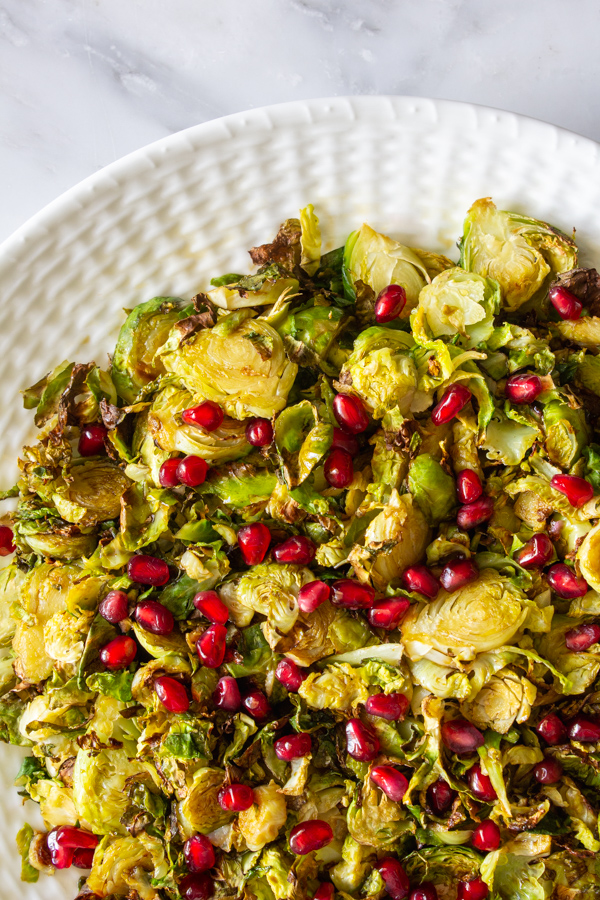 Shaved and roasted no bacon Brussels sprouts topped with pomegranate arils on a white plate.